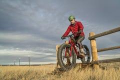 骑在牲畜看守员的一辆山肥胖自行车 库存图片