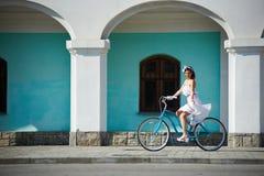 骑在绿松石墙壁前面的微笑的美丽的女性一辆蓝色自行车 库存照片