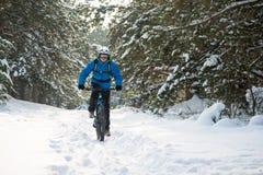骑在美丽的冬天森林极端体育和Enduro骑自行车的概念的蓝色的骑自行车者登山车 免版税库存图片