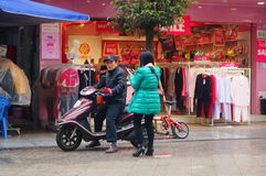 骑在街道的男人和妇女电自行车 免版税库存照片