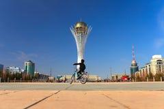 骑在都市场面的无忧无虑的孩子一辆自行车 免版税库存图片