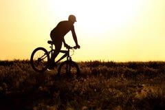 骑在领域的一个人的剪影一辆自行车 库存图片