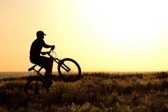 骑在领域的一个人的剪影一辆自行车 图库摄影