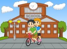 骑在他们的学校动画片前面的小孩一辆自行车 免版税图库摄影