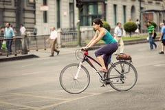 骑在Alcala街,马德里的妇女一辆自行车 免版税库存照片