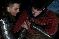 骑士帮助另一个受伤的骑士 免版税库存照片