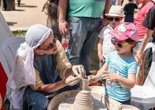 骑士节日参加者在以色列告诉一个小访客如何使黏土投手在陶瓷工` s把戈伦公园引入 免版税库存照片