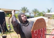 骑士节日的访客在摆在为摄影师的中世纪战士的装甲穿戴了在戈伦公园在以色列 库存照片