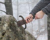骑士设法去除在石头的Excalibur剑 图库摄影