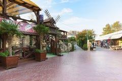 骑士雕塑入口的对餐馆和餐厅倒空秋天在黑色的步行散步Paralia 免版税库存图片