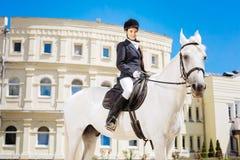 骑她的白马的典雅的柔和的妇女在大赛马跑道 免版税图库摄影