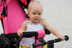 骑她的第一辆自行车的逗人喜爱的女婴 免版税库存照片