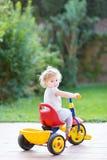 骑她的第一辆自行车的逗人喜爱的愉快的微笑的女婴 免版税库存照片