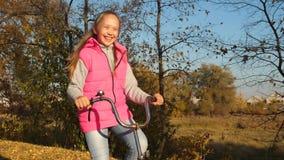 骑她的自行车和微笑在秋天公园的愉快的女孩在黄色树背景  影视素材