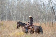 骑她的马的女牛仔 免版税库存图片