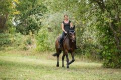 骑她的马的少妇 免版税库存照片