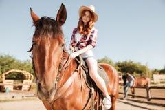骑她的马的帽子的可爱的年轻红头发人女牛仔 库存图片