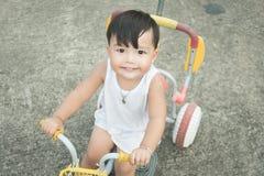 骑小自行车和看照相机的快乐婴孩在c 免版税库存图片
