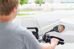 骑摩托车的少年在街口 库存图片