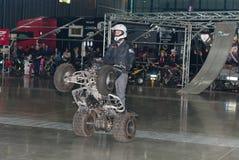 骑方形字体自行车,在特技展示期间的ATV的替身演员 库存照片