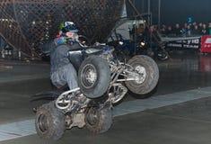 骑方形字体自行车,在特技展示期间的ATV的替身演员 库存图片