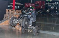 骑方形字体自行车ATV的替身演员在特技展示期间 库存照片