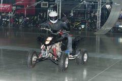 骑方形字体自行车ATV的替身演员在特技展示期间 免版税图库摄影
