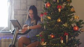 骑有一个巧妙的时钟的年轻人相当愉快的妇女一辆固定式自行车在圣诞节假日以后在圣诞节旁边 库存图片