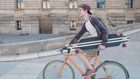 骑有一个滑板的一个愉快的人一辆自行车在他的手上在市区 影视素材