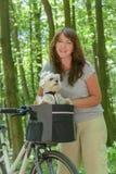 骑有她的狗的妇女一辆自行车 免版税库存图片
