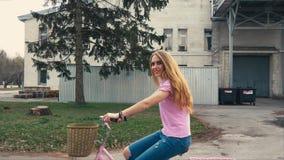 骑有篮子的俏丽的红头发人姜女孩一辆自行车在街道在夏天城市公园 股票录像