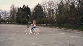骑有篮子的俏丽的红头发人姜女孩一辆自行车在街道在夏天城市公园 股票视频