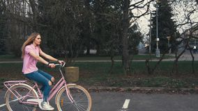 骑有篮子的俏丽的红头发人姜女孩一辆自行车在街道在夏天城市公园 影视素材