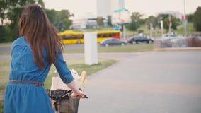 骑有花和法国面包的旁边和后面观点的女孩一辆自行车在篮子在城市,缓慢的mo, steadicam射击 股票录像