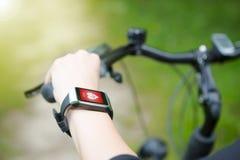 骑有smartwatch心率显示器的妇女一辆自行车 免版税库存照片