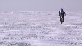 骑横跨一个冻湖的一个嬉戏人一辆自行车 股票录像