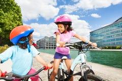 骑沿河堤防的非洲孩子自行车 免版税库存照片