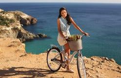 骑沿沿海的俏丽的微笑的女孩一辆自行车 免版税库存图片