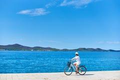 骑沿石边路的妇女一辆自行车在蓝色闪耀的海水 图库摄影