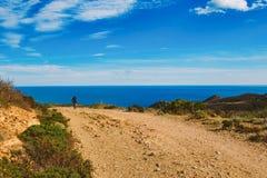 骑登山车的一个年轻人在一条自行车路线在路的西班牙以地中海为背景 免版税库存照片