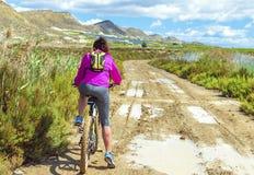 骑登山车的妇女由土一条泥泞的道路  免版税库存照片
