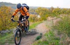 骑登山车的桔子的骑自行车者在秋天岩石足迹 极端体育和Enduro骑自行车的概念 免版税图库摄影