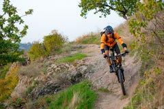 骑登山车的桔子的骑自行车者在秋天岩石足迹 极端体育和Enduro骑自行车的概念 免版税库存照片