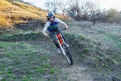 骑登山车的Enduro骑自行车者在岩石足迹 库存照片