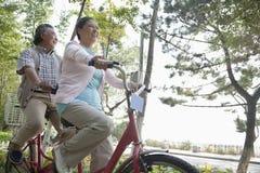 骑纵排自行车,北京的更旧的夫妇 免版税库存照片