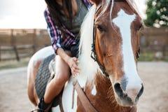 骑美丽的马的妇女女牛仔在村庄 免版税库存照片