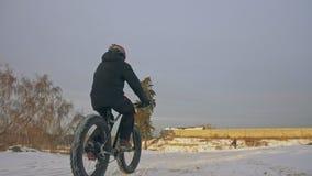 骑肥胖自行车的专业极端运动员骑自行车的人在户外 骑自行车者乘驾在雪原,森林人的冬天 股票录像