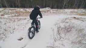 骑肥胖自行车的专业极端运动员骑自行车的人在户外 骑自行车者乘驾在雪原,森林人的冬天 影视素材