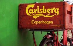 骑自行车与在篮子的一个Calsberg标题 库存照片