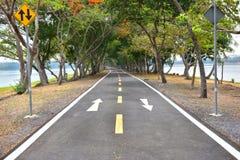 骑自行车与白色箭头标志标号的车道路面上 免版税库存照片